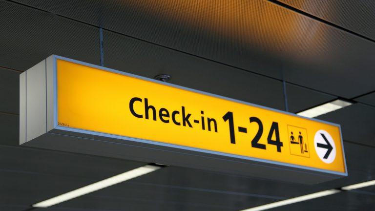 """שלט נמל תעופה צ'ק-אין - פתרונות ביטוח נסיעות לחו""""ל"""